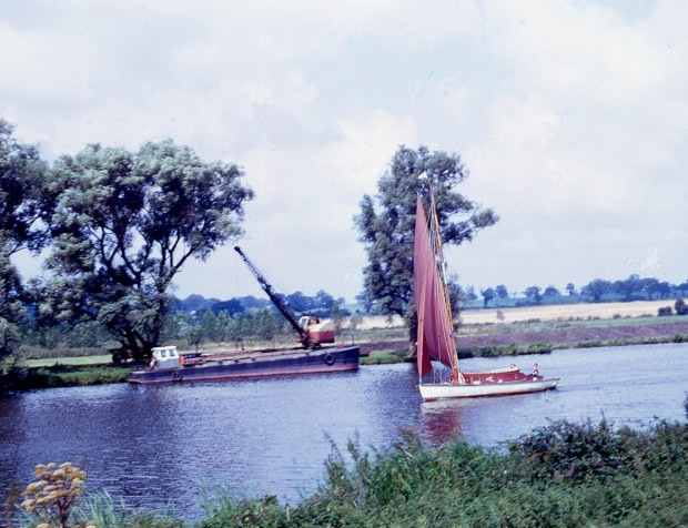 A yacht passing a dredger, on the river Yare c1970